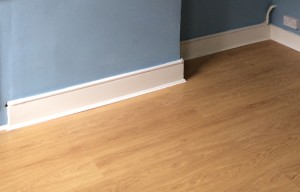 laminate flooring and gas pipe running along the top of the skirting board