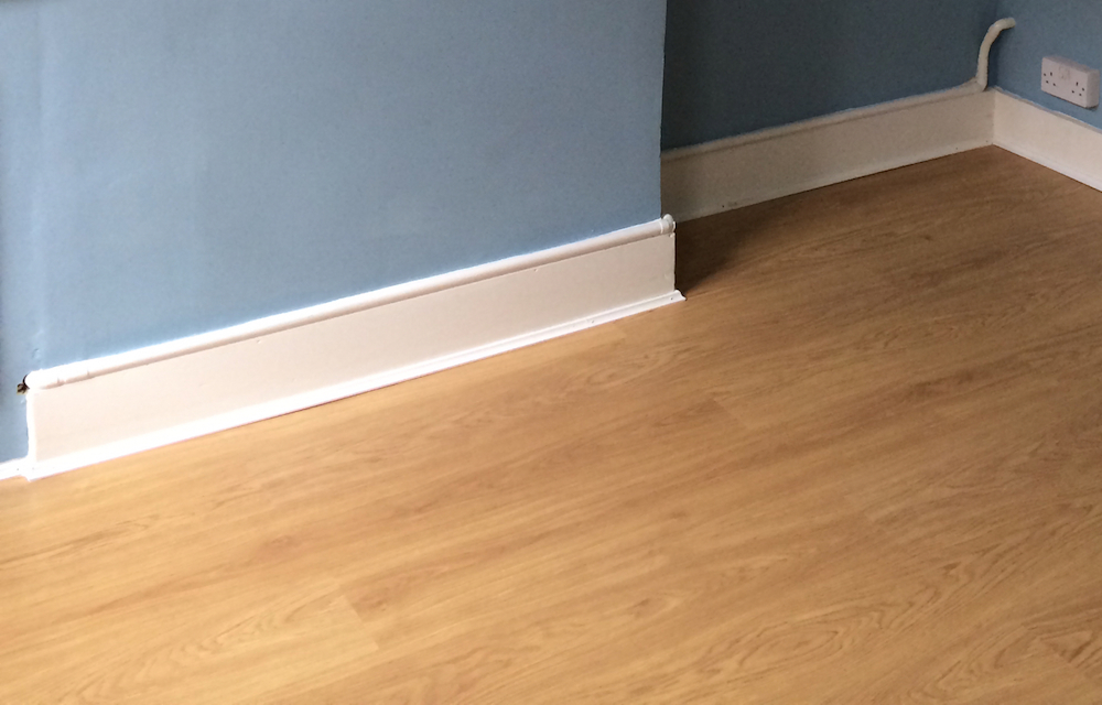 Laminate Flooring And Gas Pipe Running Along The Top Of Skirting Board
